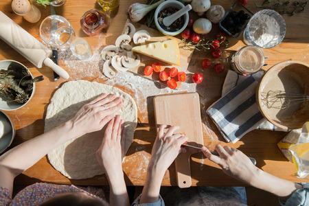 mujeres cocinando: Dos mujeres que cocinan pizza en casa. Llenar la pizza con los ingredientes. Vista superior. Vista de arriba. Foto de archivo