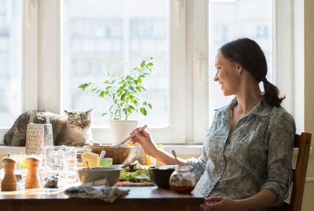 Woman cooking pizza at home. Filling dough with ingredients, while cat relaxing on window photo