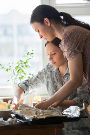 mujeres cocinando: Dos mujeres que cocinan pizza en casa. Llenado pizza con ingredientes