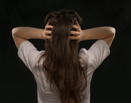 Medical doctor woman holding her head. Headache. Rear view photo