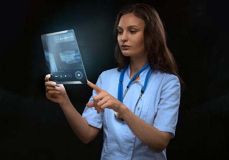 future medicine: Doctor examining an arm bones radiography using modern tablet computer
