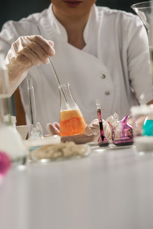 Unrecognizable science professional working with the glass cuvette photo