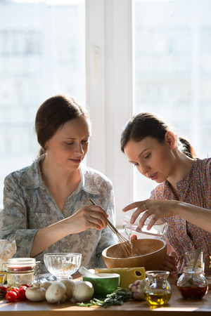 Women cooking pizza at home. Two women kneading dough photo