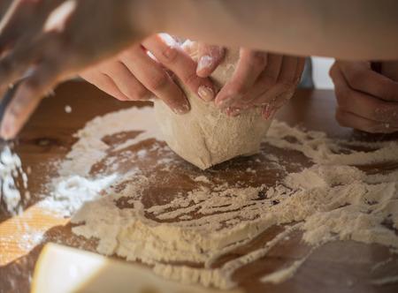 mujeres cocinando: Las mujeres que cocina la pizza en casa. Dos mujeres irreconocibles que amasan la pasta