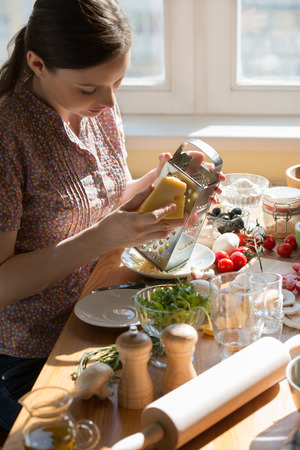 Woman cooking pizza at home. Grating cheese Stock Photo