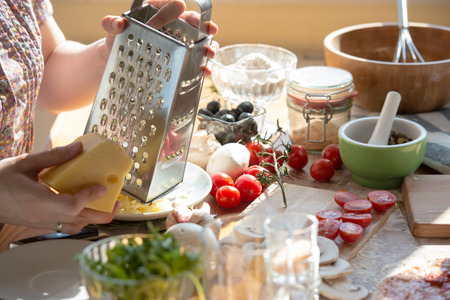kitchen ware: Woman cooking pizza at home. Unrecognizable woman grating cheese