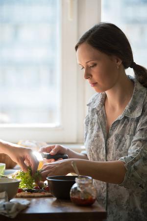 mujeres cocinando: Dos mujeres que cocinan pizza en casa. Llenado de pizza con ingredientes