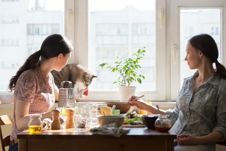 mujeres cocinando: Dos mujeres que cocinan pizza en casa. Llenado pizza con ingredientes y alimentaci�n lindo gato