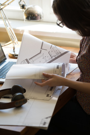 Woman working at home with laptop and architecture plan photo