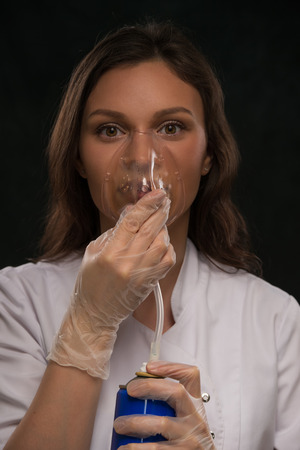 o2: Female doctor holding can with oxygen and breathing through the mask
