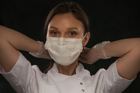 Portrait of female doctor putting on mask over black background Stock Photo