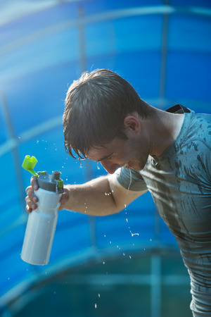 hot water: Young tired athlete splashing and pouring fresh water on his head to refresh during a running trail