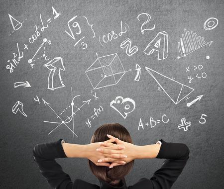 simbolos matematicos: Joven estudiante en la universidad con los s�mbolos matem�ticos de arriba. Concepto de la educaci�n