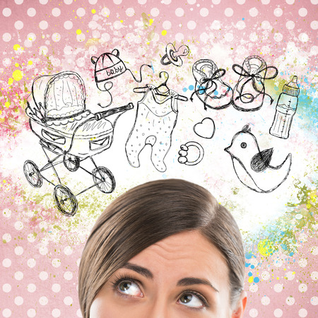 positive thinking: Young woman thinking of her pregnancy plans closeup face portrait and sketches overhead Stock Photo