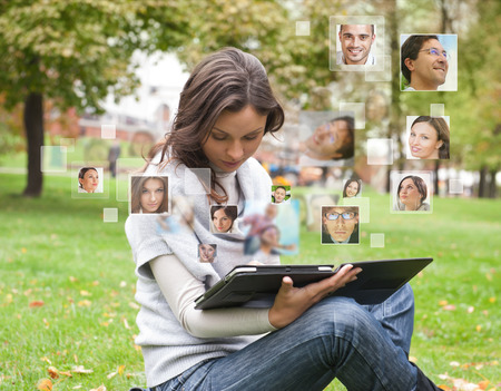 Young woman using tablet computer with many different people's faces around her. Technology social media network of friends and communication.