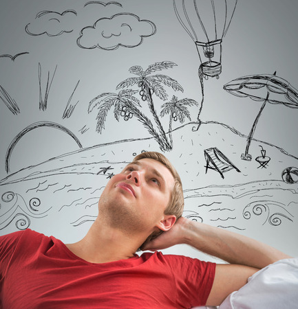 Young man dreaming about his summer vacation on tropical island photo