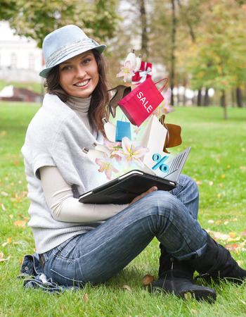 Woman shopping online using her tablet computer outdoors at summer park photo