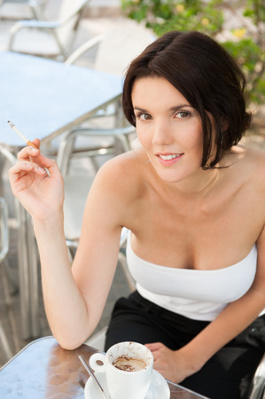 sexy girl smoking: Portrait of a beautiful woman smokes a cigarette outdoor at cafe Stock Photo