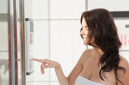 Woman dialing intercom photo