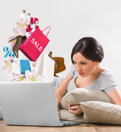 Woman shopping online using her laptop at home photo