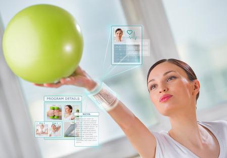 Mujer que hace ejercicio con la bola usando dispositivo port�til inteligente con interfaz futurista Foto de archivo