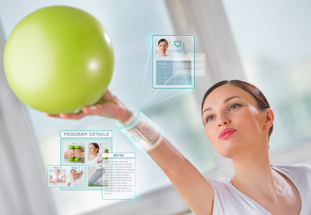 hologram: Woman doing exercise with ball wearing smart wearable device with futuristic interface