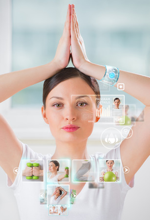 sport training: Woman doing exercise wearing smart wearable device with futuristic interface  Stock Photo