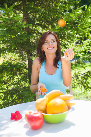 Happy Smiling Young Woman Juggling Oranges at her Garden photo