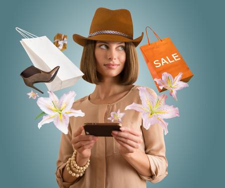 shopping: Compras de la mujer en la aplicaci�n usa su tel�fono inteligente Foto de archivo