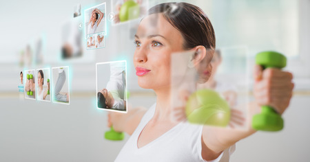 現代の仮想インターフェイスを使用してワークアウト スポーティな女性。オンラインのフィットネス トレーナーの概念