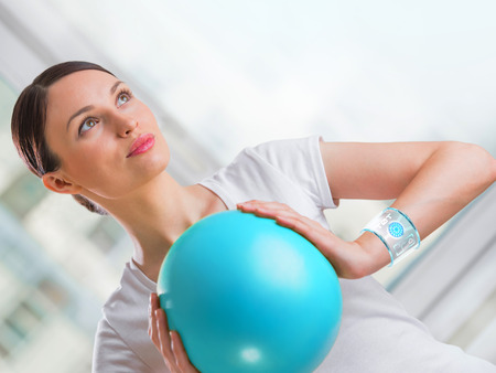 training device: Portrait of modern healthy woman wearing smart watch device with touchscreen doing exercises Stock Photo