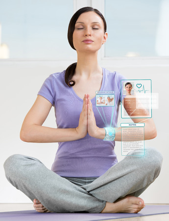 wearable: Woman doing exercise wearing smart wearable device with futuristic interface Stock Photo