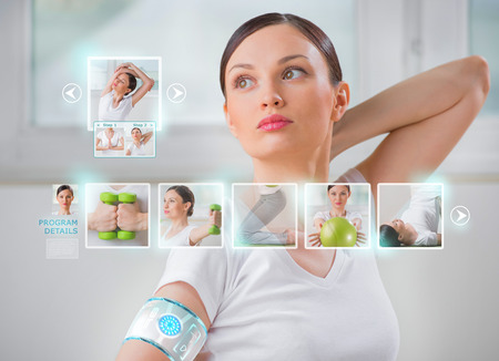 Woman doing exercise wearing smart wearable device with futuristic interface  Stok Fotoğraf