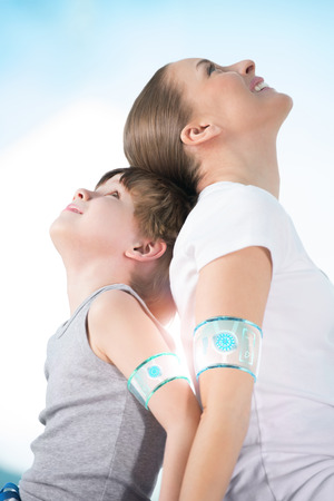 looking upwards: Mother and son wearing smart watch device sitting back to back together and looking upwards  Stock Photo
