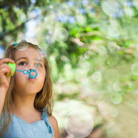 five years old: Cinque anni caucasico ragazza che soffia bolle di sapone all'aperto presso il parco in estate - felice spensierata infanzia Archivio Fotografico