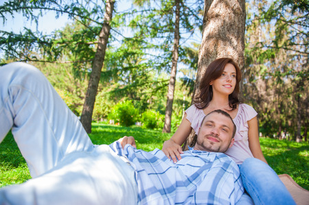 Adult couple picnicking in the summer park under the tree photo