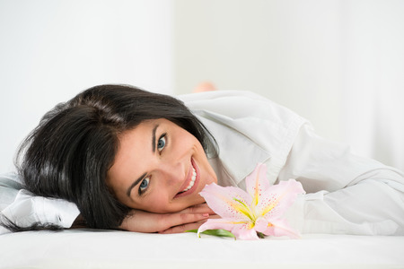 Front view of young woman relaxing on massage table in health spa photo