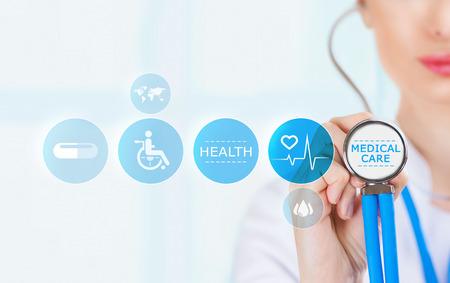 estetoscopio: Doctor en medicina mano sosteniendo el estetoscopio y el trabajo con los iconos de la medicina moderna