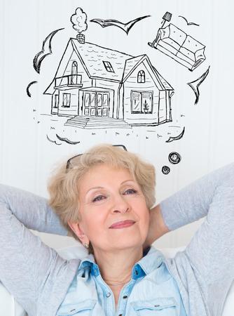 Hypotheek en krediet concept. Senior vrouw droomt over het comfort pensioen