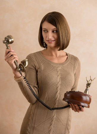 Happy elegant woman talking on retro telephone photo