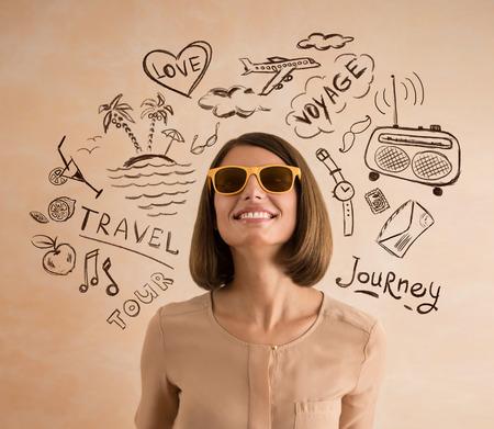 soñando: Mujer sonriente positiva con gafas de sol que planean sus vacaciones. Bocetos de sus planes de viaje a su alrededor Foto de archivo