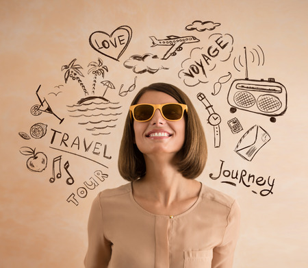 Positive smiling woman wearing sunglasses planning her vacation. Sketches of her plans of trip around her Stok Fotoğraf