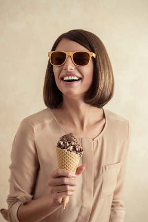 ice cream woman: Ice cream woman singing in cone like in microphone happy, joyful and cheerful. Cute young female model eating ice cream cone