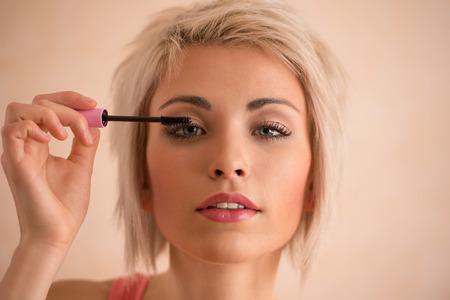 Elegant blonde beauty doing makeup photo