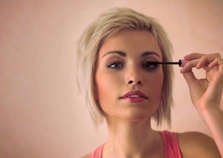 girl short hair: Elegant blonde beauty doing makeup