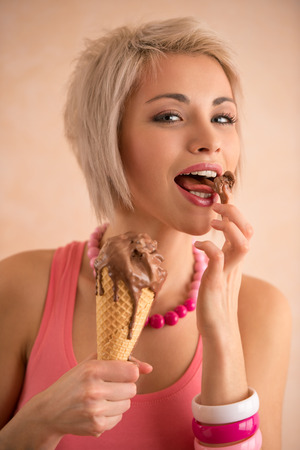 Young pretty girl with short blond hair eating melting chocolate ice cream in cone. 100% satisfaction photo