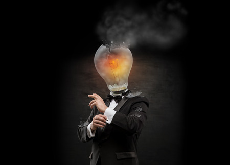 overpowered: Businessman with exploded overworked lamp head on black background.