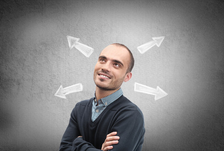 Confident, young businessman looking at chalk drawn arrows on a concrete wall photo