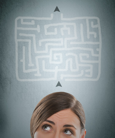 Young businesswoman looking at the labyrinth and thinking about right way photo