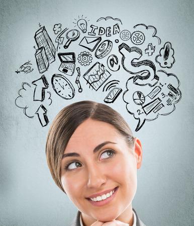 Jonge zaken vrouw denken van haar plannen close-up gezicht portret en schetsen overhead